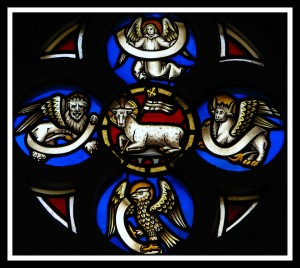 Animal icons of the four gospels on stained glass. Clockwise: angel, bull, eagle, lion